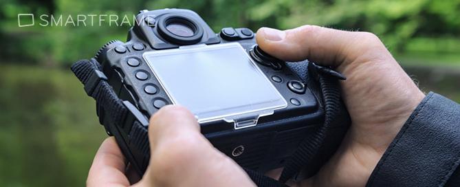 Man adjusting settings on his DSLR camera. Image: Shutterstock.com